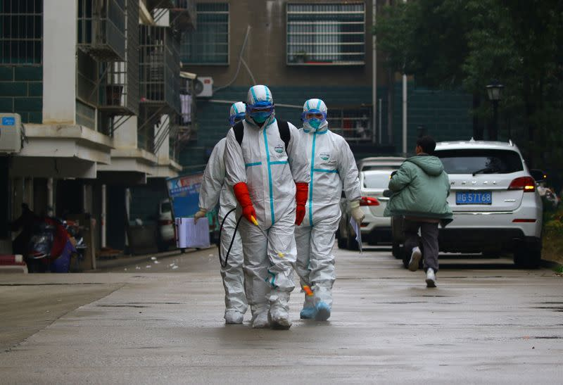 Workers from local disease control and prevention department in protective suits disinfect a residential area following the outbreak of a new coronavirus, in Ruichang, Jiangxi
