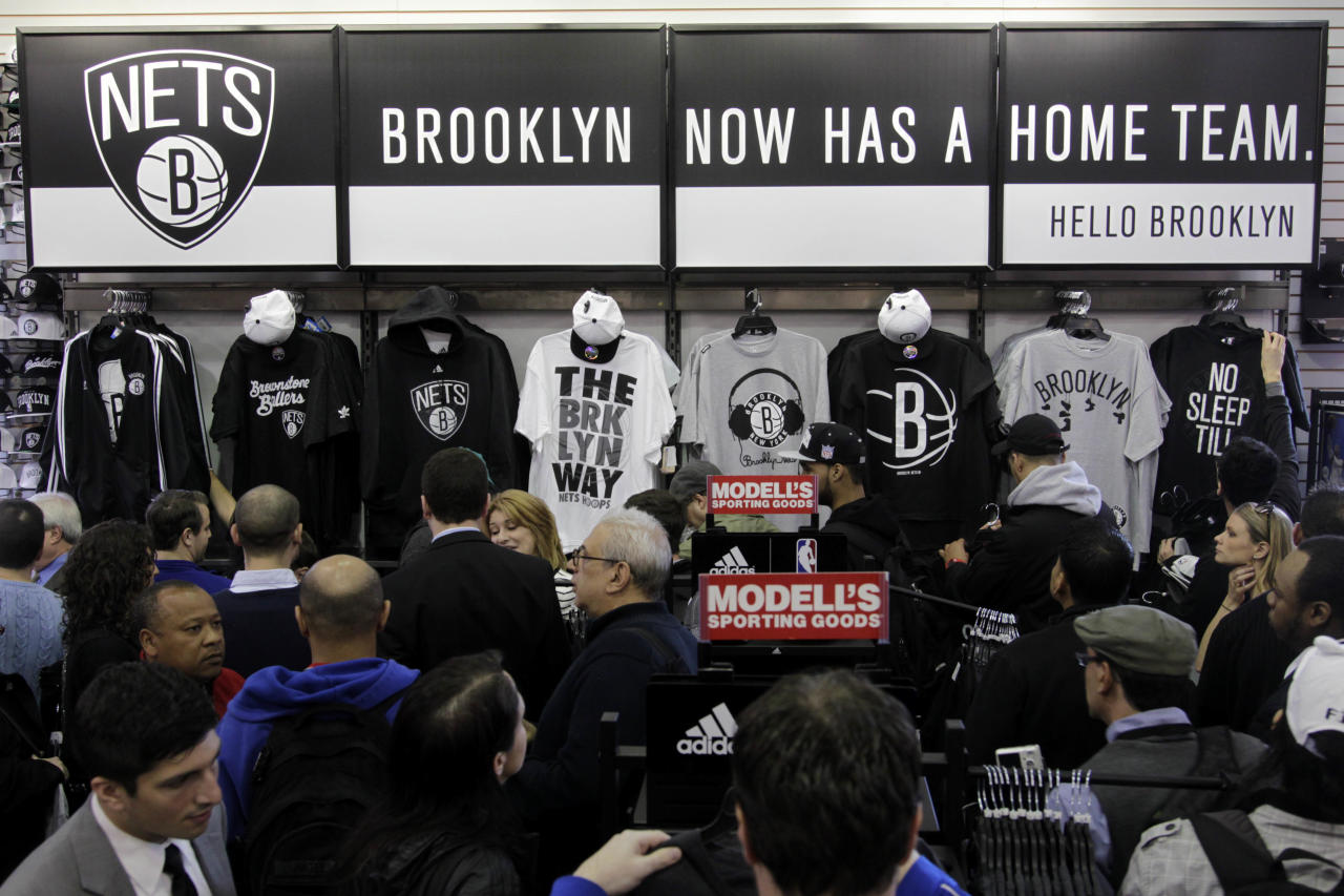People shop for merchandise bearing the new logos of the Brooklyn Nets basketball team, in the Brooklyn borough of  New York, Monday, April 30, 2012. The Nets will be moving from New Jersey to the new Barclays Center in Brooklyn for the 2012-2013 NBA basketball season. (AP Photo/Seth Wenig)