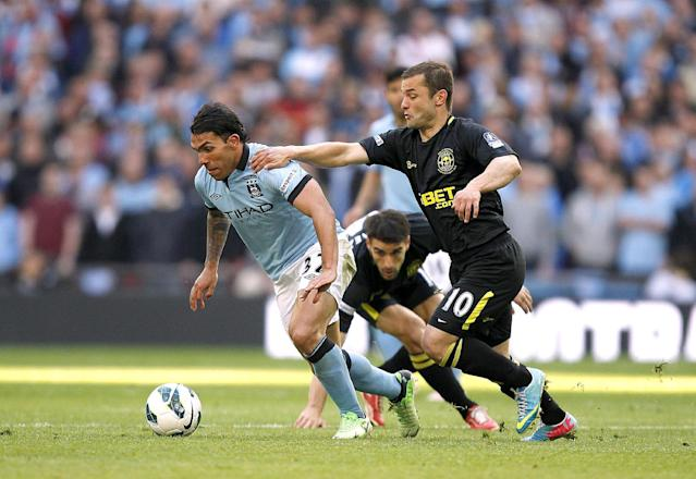 Manchester City's Carlos Tevez and Wigan Athletic's Shaun Maloney (right) battle for the ball