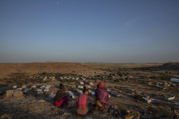 Tigray women who fled the conflict in Ethiopia's Tigray region, sit on a hill top overlooking Umm Rakouba refugee camp, in Qadarif, eastern Sudan, Thursday, Nov. 26, 2020. Ethiopia's prime minister said Thursday the army has been ordered to move on the embattled Tigray regional capital after his 72-hour ultimatum ended for Tigray leaders to surrender, and he warned the city's half-million residents to stay indoors and disarm. (AP Photo/Nariman El-Mofty)