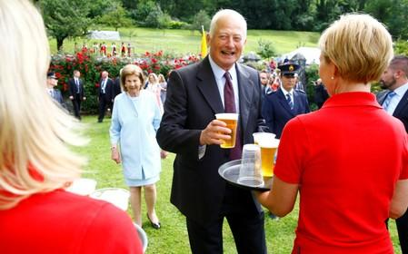 Prince Hans-Adam II of Liechtenstein takes a beer from a waitress as wife Princess Marie stands behind him during a party in the gardens of Schloss Vaduz castle in Vaduz