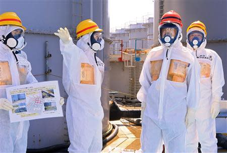 Japan's Prime Minister Shinzo Abe (2nd R), wearing protective suit and mask, is briefed about tanks containing radioactive water by Fukushima Daiichi nuclear power plant chief Akira Ono (2nd L), as they stand near a tank (C, with railings painted red and blue) which is being dismantled after leaking contaminated water, during his inspection tour to the Tokyo Electric Power Co. (TEPCO)'s tsunami-crippled Fukushima Daiichi nuclear power plant in Okuma, Fukushima Prefecture, in this file picture taken September 19, 2013. REUTERS