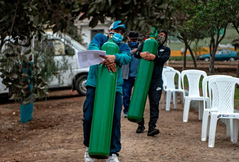 Relatives of COVID-19 patients move oxygen cylinders as they queue to recharge them in Villa Maria del Triunfo, in the southern outskirts of Lima last week.