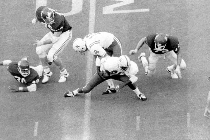 """FILE - In this Nov. 25, 1971 file photo, Nebraska's Johnny Rodgers (20) avoids Oklahoma defenders as he returns a punt for a touchdown in the first quarter of an NCAA college football game in Norman, Okla. The game, which Nebraska won 35-31, is widely remembered as """"The Game of the Century."""" (Lincoln Journal Star via AP, File)"""