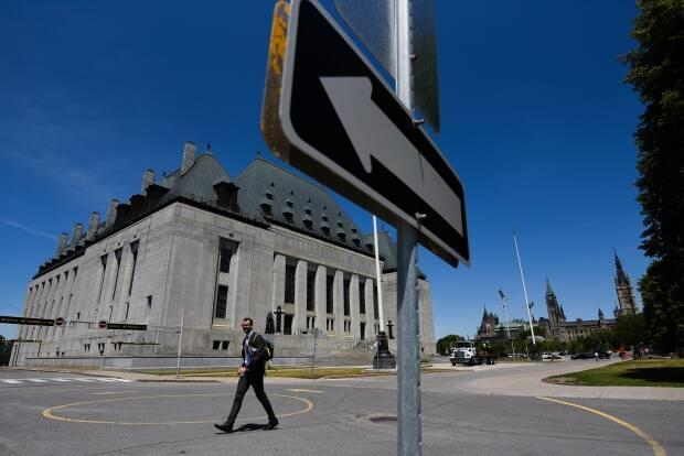 A pedestrian wears a mask as he walks in front of the Supreme Court of Canada in downtown Ottawa on June 17. (Justin Tang/The Canadian Press - image credit)