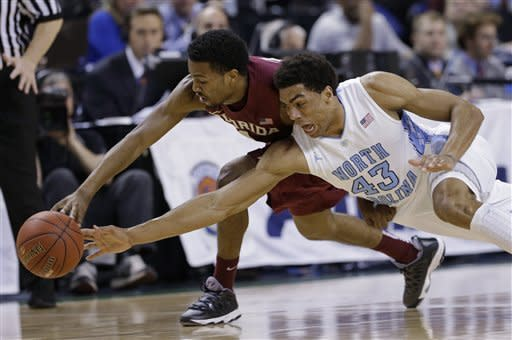 Florida State's Devon Bookert, left, and North Carolina's James Michael McAdoo, right, chase a loose ball during the first half of an NCAA college basketball game at the Atlantic Coast Conference men's tournament in Greensboro, N.C., Friday, March 15, 2013. (AP Photo/Gerry Broome)