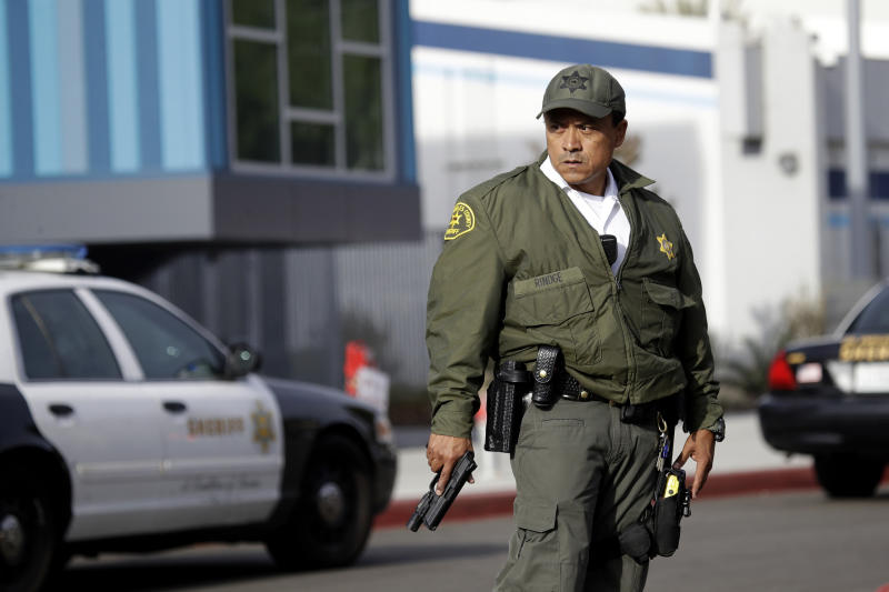 A member of the Los Angeles County Sheriff Department stands outside of Saugus High School with his weapon drawn after reports of a shooting on Nov. 14, 2019, in Santa Clarita, Calif. (Photo: Marcio Jose Sanchez/AP)