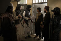 Taliban fighters talk to a detainee before transferring him to a court in Kabul, Afghanistan, Sunday, Sept. 19, 2021. The Taliban are shifting from being warriors to an urban police force. (AP Photo/Felipe Dana)
