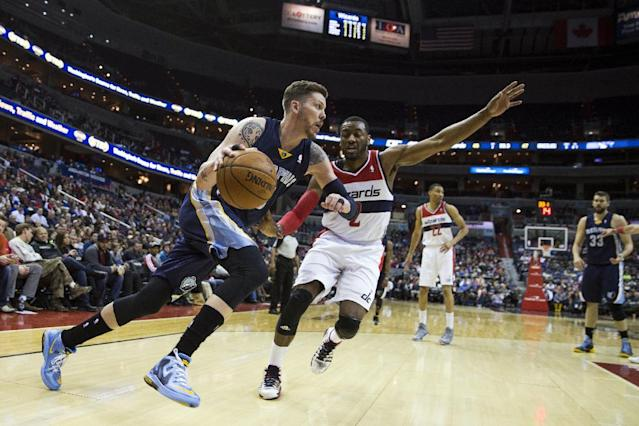 Memphis Grizzlies forward Mike Miller, left, drives past Washington Wizards guard John Wall during the first half of an NBA basketball game on Monday, March 3, 2014, in Washington. (AP Photo/ Evan Vucci)
