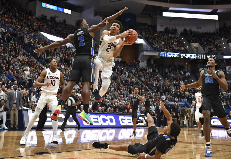 Connecticut's James Bouknight (2) is fouled by Memphis' Alex Lomax (2) as he goes up for a basket in the second half of an NCAA college basketball game, Sunday, Feb. 16, 2020, in Hartford, Conn. (AP Photo/Jessica Hill)