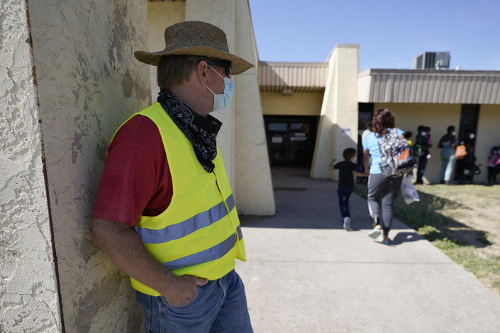 Dave, left, who declined to give his last name, from Toledo, Ohio, wears a neon vest as migrants are released from U.S. Customs and Border Protection custody, Friday, Sept. 24, 2021, in Del Rio, Texas. Dave, who has been to Haiti many times, befriended a woman named Ruth, who he believes is still in custody after she crossed the Rio Grande with her husband and their 3-year-old daughter. Dave drove down from Ohio to Southwest Texas in hopes of picking the family up and driving them to Ohio, where Ruth has family awaiting them. (AP Photo/Julio Cortez)