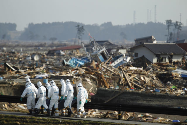 Japanese police officers carry a body during search and recovery operation for missing victims in the area devastated by the March 11 earthquake and tsunami in Namie, Fukushima Prefecture, northeastern Japan, Friday, April 15, 2011. In the background is part of the Fukushima Dai-ichi nuclear complex.