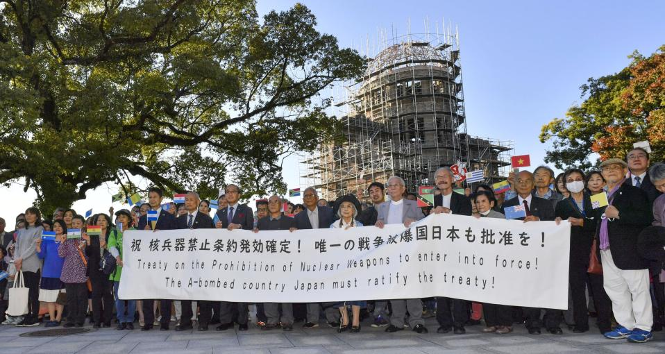 Members of Atomic Bomb survivors groups gather, holding a banner calling for Japanese government to ratify the Treaty on the Prohibition of Nuclear Weapons, with the Atomic Bomb Dome in background, in Hiroshima, western Japan, Sunday, Oct. 25, 2020. The United Nations confirmed Saturday that 50 countries have ratified the Treaty on the Prohibition of Nuclear Weapons, known as the TPNW, paving the way for its entry into force in 90 days. (Kyodo News via AP)