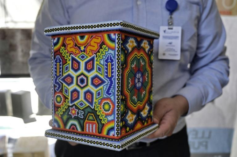 Roberto Garcia, director of the Olimpia funeral home in Mexico City, holds an urn decorated with indigenous Wixarika motifs