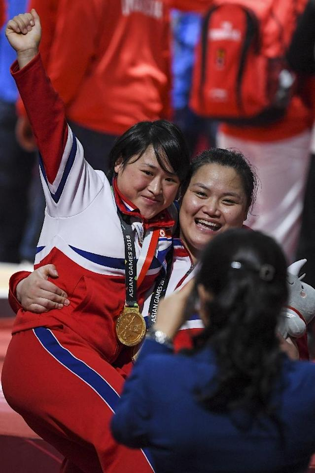 Little and large: Kim Kuk Hyang carries Ri Song Gum around as North Korea celebrated their record weightlifting haul (AFP Photo/CHAIDEER MAHYUDDIN)