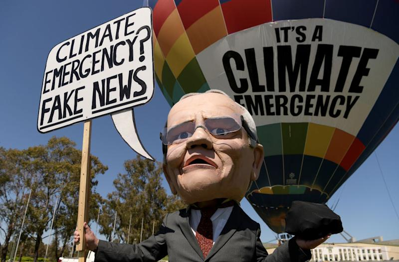"A mannequin of Prime Minister Scott Morrison holding a sign saying ""Climate emergency? Fake News""."