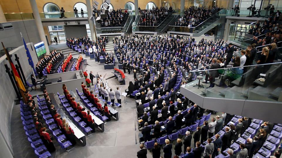 People hold a minute of silence in tribute to victims of Friday's attacks in Paris, during a ceremony marking the National Day of Mourning in the Bundestag in Berlin, Germany, November 15, 2015. The annual ceremony commemorates all who have died in armed conflict or as the victims of violent oppression. REUTERS/Hannibal Hanschke