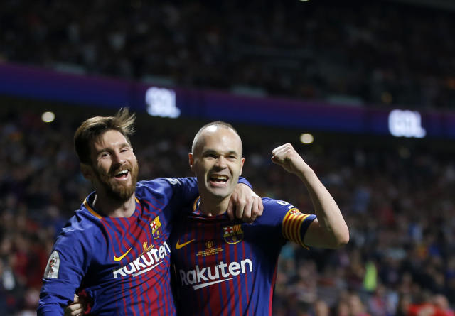 Barcelona's Andres Iniesta, right, celebrates withLionel Messi after scoring his side's fourth goal during the Copa del Rey final soccer match between Barcelona and Sevilla at the Wanda Metropolitano stadium in Madrid, Spain, Saturday, April 21, 2018. (AP Photo/Paul White)