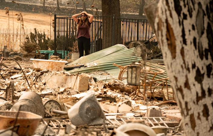 Alyssa Medina looks over the charred remains of her family home during the LNU Lightning Complex Fire in Vacaville, Calif., on Aug. 23.