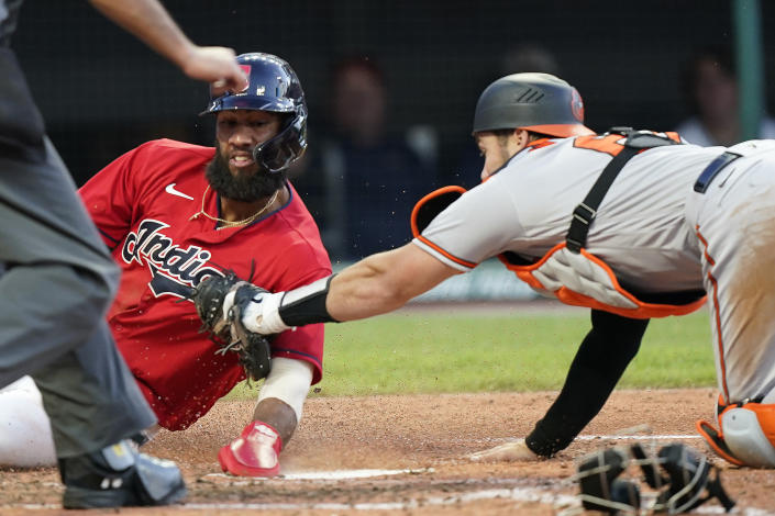 Cleveland Indians' Amed Rosario, left, scores as Baltimore Orioles catcher Austin Wynns is late on the tag in the fourth inning of a baseball game, Tuesday, June 15, 2021, in Cleveland. (AP Photo/Tony Dejak)