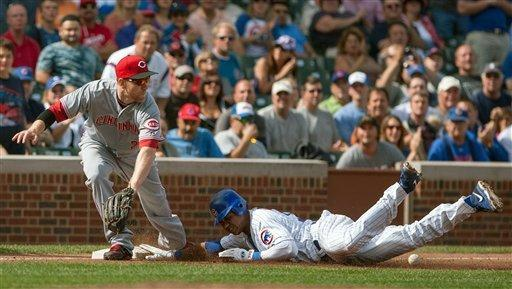 Chicago Cubs' Starlin Castro beats the ball to third with a triple in the fourth inning as Cincinnati Reds third baseman Todd Frazier reaches for the late throw in a baseball game in Chicago on Thursday, Sept. 20, 2012. (AP Photo/Charles Cherney)