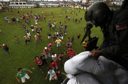 A Philippine Air Force crew drops sacks containing food supplies to Typhoon Haiyan survivors in Tunga