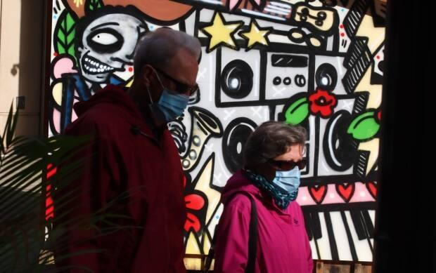 Two people wearing masks walk past a mural installed on an outdoor stage on Sparks Street on Sunday. (Trevor Pritchard/CBC - image credit)