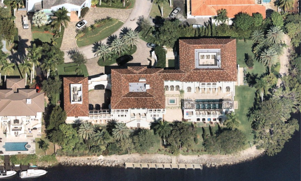 An aerial view shows the 17,000-square-foot mansion and its water frontage.