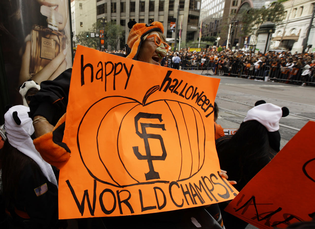 Pearl Garvin, of Mountain View, Calif., holds a sign while waiting on Market Street for the start of the San Francisco Giants World Series victory parade Wednesday, Oct. 31, 2012, in San Francisco. The team's second championship in three years goes along Market Street and ends with a celebration in front of City Hall. (AP Photo/Eric Risberg)