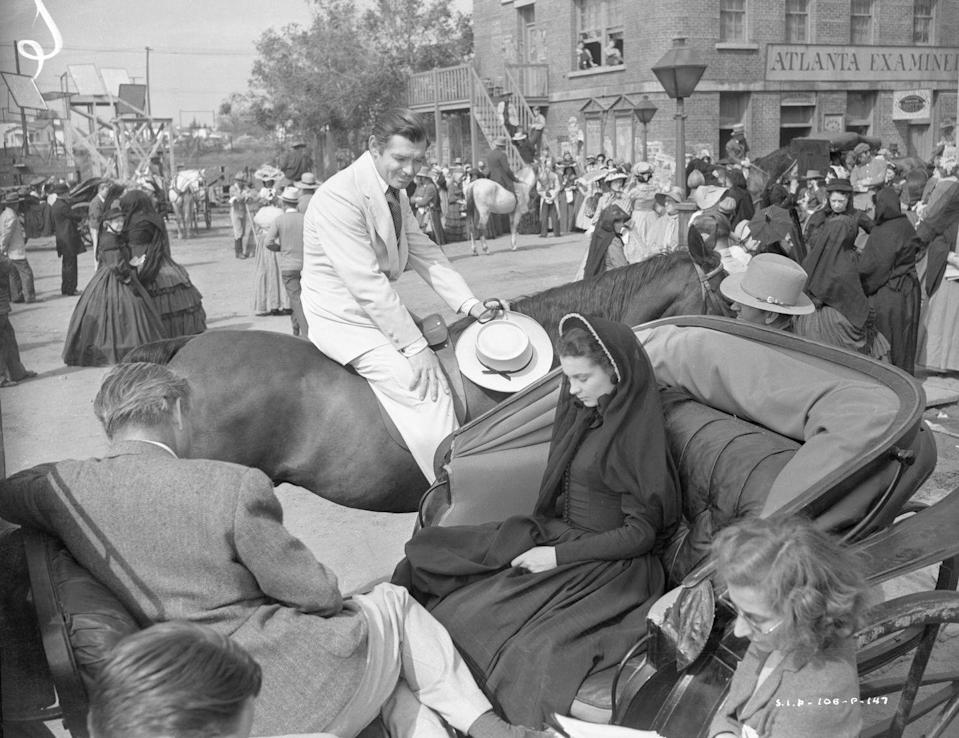 <p>Director Victor Fleming sits in a carriage with lead actress, Vivien Leigh, as she and costar Clark Gable (on horseback) rehearse their lines. </p>