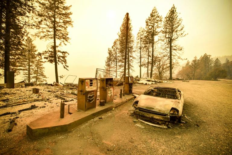 "A burnt car and a gas station remain visible on November 11, 2018 after the ""Camp"" fire tore through the region near Pulga, east of Paradise, California"