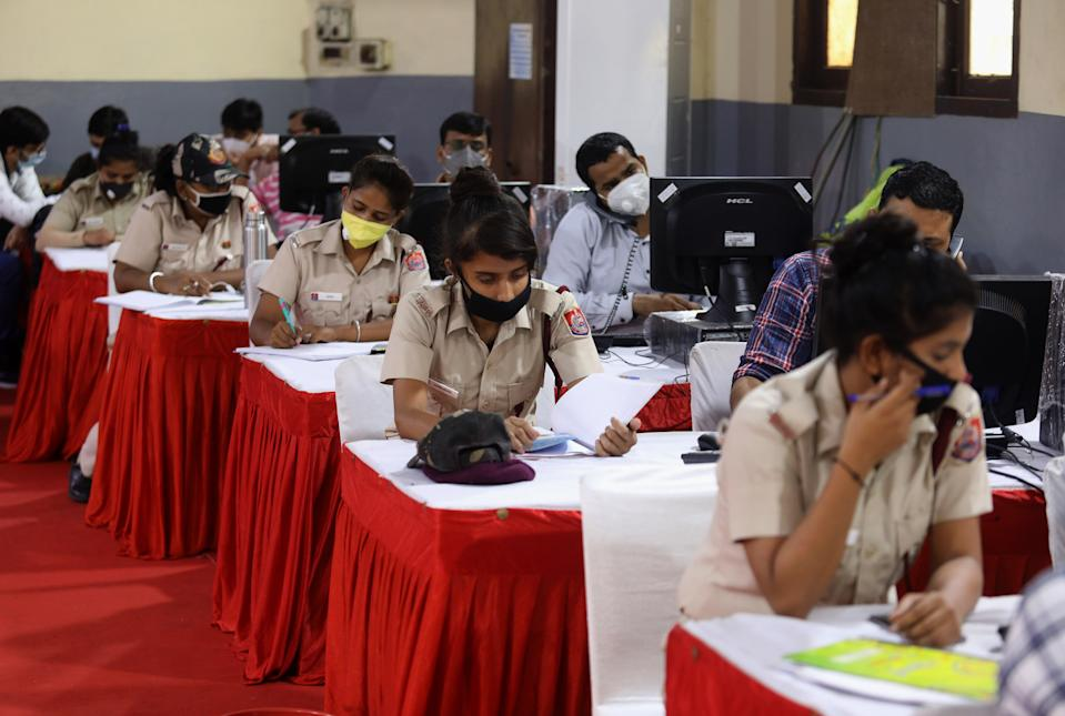 Indian volunteers from Delhi Civil Defence (DCD) wearing face masks work at the COVID-19 District Central Surveillance and Tele-medicine Hub to serve as a free help line service for the COVID-19 patients and their families.The Doctors and Counsellors update data, register all grievances, daily health status of COVID-19 patients and prevent them from getting critical, provide Medical help, sanitation and removal of biomedical waste and provide them with essential commodities. This was launched at the office of the District Magistrate of the central district at Daryaganj. (Photo by Naveen Sharma/SOPA Images/LightRocket via Getty Images)