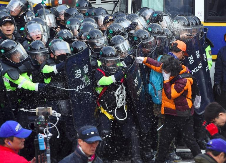 Supporters of South Korean President Park Geun-Hye clash with police in Seoul on March 10, 2017 after the Constitutional Court upheld her impeachment