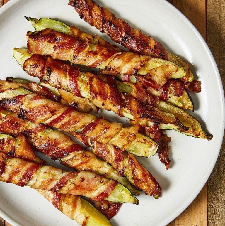 """<p>Anything wrapped in <a href=""""https://www.delish.com/uk/cooking/recipes/a30208165/how-to-cook-bacon-in-the-oven-recipe/"""" rel=""""nofollow noopener"""" target=""""_blank"""" data-ylk=""""slk:bacon"""" class=""""link rapid-noclick-resp"""">bacon</a> is instantly 1,000 times better. These 'fries' are simply roasted courgette wedges wrapped in bacon and let's just say...courgette has never tasted so good. </p><p>Get the <a href=""""https://www.delish.com/uk/cooking/recipes/a35187270/bacon-zucchini-fries-recipe/"""" rel=""""nofollow noopener"""" target=""""_blank"""" data-ylk=""""slk:Bacon Courgette Fries"""" class=""""link rapid-noclick-resp"""">Bacon Courgette Fries</a> recipe.</p>"""