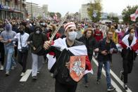 """Demonstrators, one of them wearing an old Belarusian nation flag and holding a cardboard sword reading """"solidarity"""" march during an opposition rally to protest the official presidential election results in Minsk, Belarus, Sunday, Sept. 27, 2020. Hundreds of thousands of Belarusians have been protesting daily since the Aug. 9 presidential election. (AP Photo/TUT.by)"""
