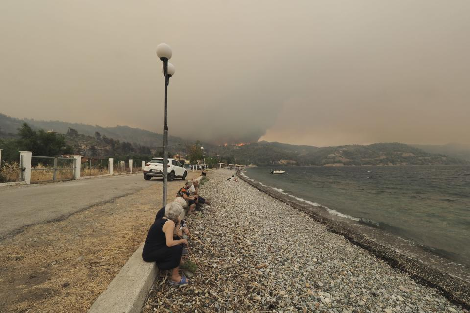 People sit on the beach as a wildfire approaches Limni village on the island of Evia, about 160 kilometers (100 miles) north of Athens, Greece, Friday, Aug. 6, 2021. Thousands of people fled wildfires burning out of control in Greece and Turkey on Friday, including a major blaze just north of the Greek capital of Athens that claimed one life, as a protracted heat wave left forests tinder-dry and flames threatened populated areas and electricity installations. (AP Photo/Thodoris Nikolaou)