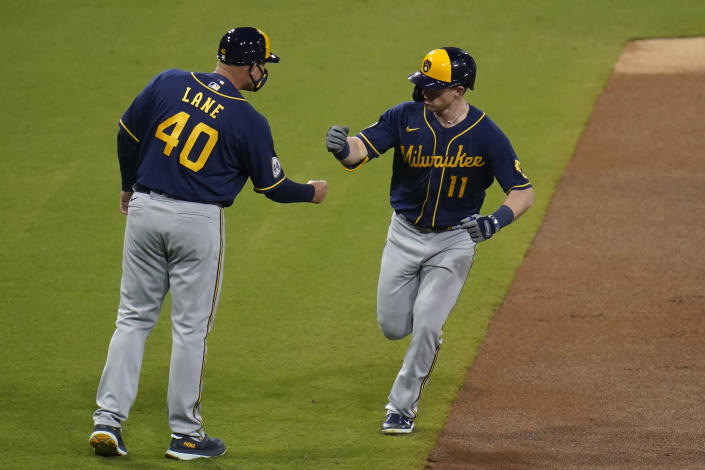 Milwaukee Brewers' Billy McKinney, right, reacts with third base coach Jason Lane (40) after hitting a home run during the third inning of a baseball game against the San Diego Padres, Tuesday, April 20, 2021, in San Diego. (AP Photo/Gregory Bull)
