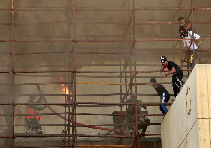 Anti-government protesters escape from a burning building during a demonstration in Baghdad, Iraq, Saturday, Oct. 26, 2019. (Photo: Hadi Mizban/AP)