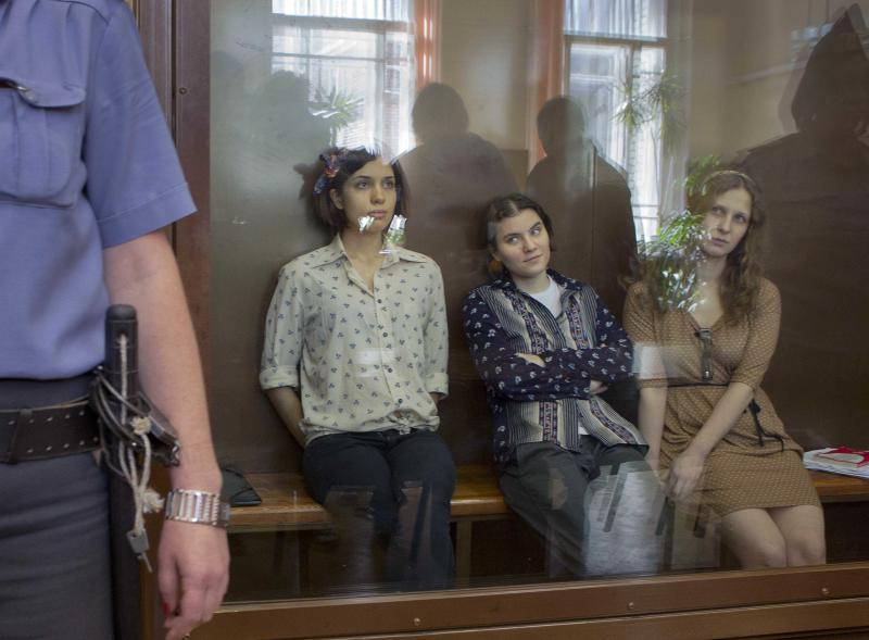 """Pussy Riot members, from left, Nadezhda Tolokonnikova, Yekaterina Samutsevich and Maria Alekhina sit in a glass cage at a court room in Moscow, Russia, Friday, Aug. 3, 2012. Russia's President Vladimir Putin on Thursday criticized the feminist punk rockers facing trial for performing a """"punk prayer"""" against him at Moscow's main cathedral, but said that a punishment for them shouldn't be too severe. (AP Photo/Misha Japaridze)"""