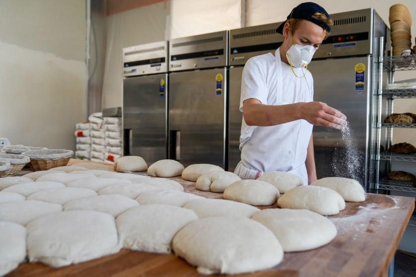 Jyan Isaac sprinkles flour on dough as he works in his kitchen at his Culver City shop.