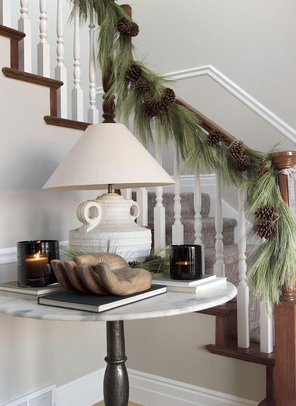 """<p>Long pine needle garland makes a stunning statement on stairs, especially when you add real pine cones. You could also do this with real roping. </p><p><strong>Get the tutorial at <a href=""""https://roomfortuesday.com/2020-holiday-home-tour/"""" rel=""""nofollow noopener"""" target=""""_blank"""" data-ylk=""""slk:Room for Tuesday."""" class=""""link rapid-noclick-resp"""">Room for Tuesday.</a></strong></p><p><a class=""""link rapid-noclick-resp"""" href=""""https://www.amazon.com/RAZ-Imports-Greenery-Needle-Garland/dp/B085LQC8PY/ref=sr_1_6?dchild=1&keywords=long+pine+needle+garland&qid=1633171537&sr=8-6&tag=syn-yahoo-20&ascsubtag=%5Bartid%7C2164.g.37723896%5Bsrc%7Cyahoo-us"""" rel=""""nofollow noopener"""" target=""""_blank"""" data-ylk=""""slk:SHOP LONG PINE NEEDLE GARLAND"""">SHOP LONG PINE NEEDLE GARLAND</a></p>"""