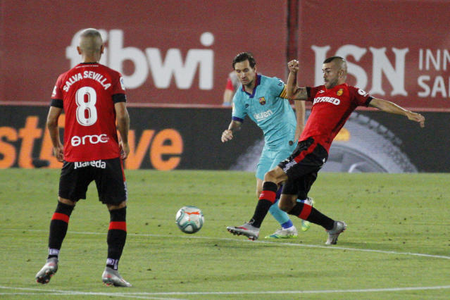 FC Barcelona's Lionel Messi in action during the Spanish La Liga soccer match between Mallorca and FC Barcelona at Son Moix Stadium in Palma de Mallorca, Spain, Saturday, June 13, 2020. With virtual crowds, daily matches and lots of testing for the coronavirus, soccer is coming back to Spain. The Spanish league resumes this week more than three months after it was suspended because of the COVID-19 pandemic. (AP Photo/Francisco Ubilla)