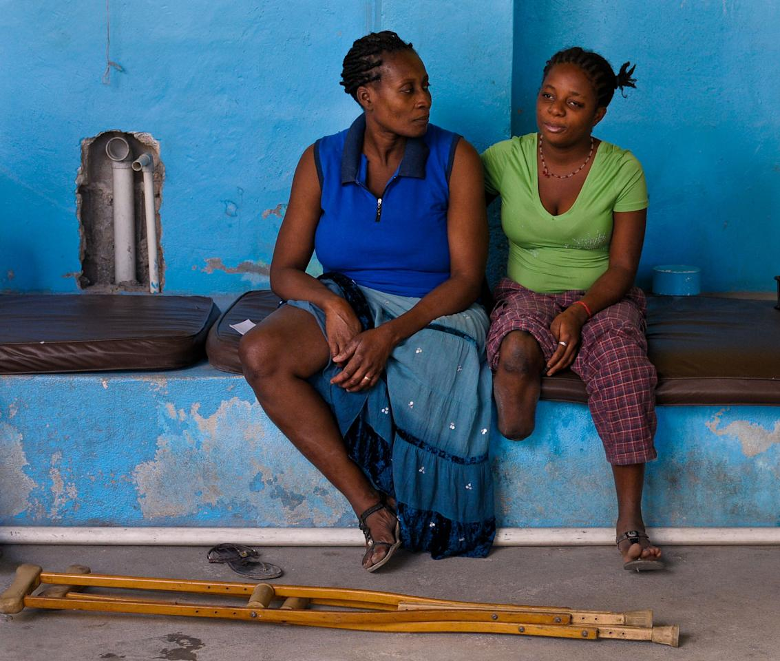 Amputee patients who have lost legs during the 2010 earthquake wait at a center run by Handicap International to undergo rehabilitative therapy in Port-au-Prince January 4, 2012. January 12 marks the second year anniversary of the devastating earthquake that killed more than 200,000 people and injured many.  REUTERS/Swoan Parker (HAITI - Tags: HEALTH DISASTER TPX IMAGES OF THE DAY)