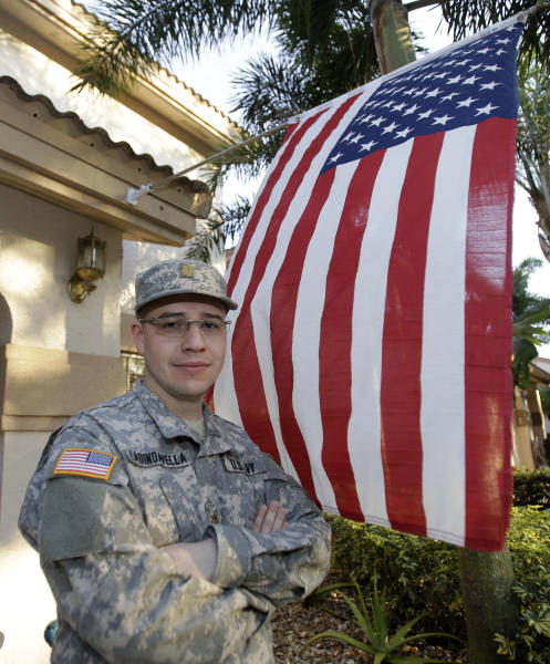 Miami physician Marco Ladino Avellaneda poses for a photo in front of his home in Plantation, Fla., Monday, Feb 25, 2013. Avellaneda was born in Bogota, Columbia, and came to the United States on a visa to study medicine. Now, he is a major in the Army Reserves and a kidney specialist at a veterans' hospital in Miami. After joining the Army Reserves, Ladino Avellaneda got his citizenship papers in a month instead of the 10 years he expected, he said in a telephone interview. And he just completed a four-month deployment to Kosovo. (AP Photo/Alan Diaz)