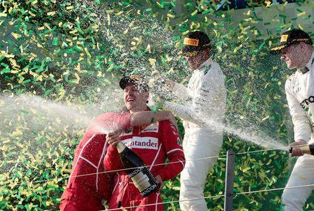 Formula One - F1 - Australian Grand Prix - Melbourne, Australia - 26/03/2017 - Ferrari driver Sebastian Vettel of Germany (2nd L) sprays champagne alongside second-placed Mercedes driver Lewis Hamilton (2nd R) of Britain and team mate Valtteri Bottas of Finland (R) on the podium. REUTERS/Jason Reed