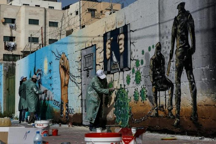 Palestinian artists paint a mural in a show of support for Palestinian prisoners held in Israeli jails amid the COVID-19 pandemic, in Gaza City on April 20 (AFP Photo/MOHAMMED ABED)