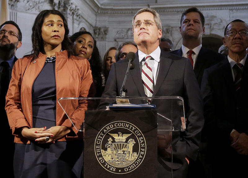 FILE - In this Dec. 12, 2017 file photo, city attorney Dennis Herrera, center, speaks at a news conference next to acting mayor London Breed, left, at City Hall in San Francisco. San Francisco officials are offering to buy Pacific Gas & Electric's power lines and other infrastructure in the city for $2.5 billion. Mayor London Breed and City Attorney Dennis Herrera presented the offer in a letter sent to the utility Friday, Sept. 6, 2019. (AP Photo/Jeff Chiu, file)