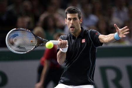 Novak Djokovic of Serbia hits a return to David Ferrer of Spain in their final match at the Paris Masters men's singles tennis tournament at the Palais Omnisports of Bercy in Paris, November 3, 2013. REUTERS/Gonzalo Fuentes