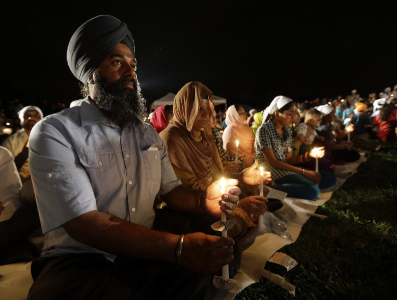 Raghu Vinder listens to speakers during a candlelight vigil in the parking lot the Sikh Temple of Wisconsin Monday, Aug. 5, 2013, in Oak Creek, Wis. Monday is the one-year anniversary of the shooting rampage when a white supremacist at the temple where six people were killed. (AP Photo/Morry Gash)