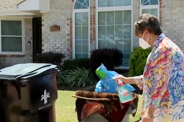 Image: New Orleans East homeowner Embra Bridges sprays bleach over her pile of trash, which she claims has not been touched since Ida hit. (WDSU)